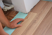 Man Installing Laminate Wood Flooring in Problem Area. Worker Installing wooden laminate flooring. Handyman laying down laminate flooring boards while renovating a house.