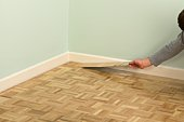 Man installing parquet floor next to skirting board
