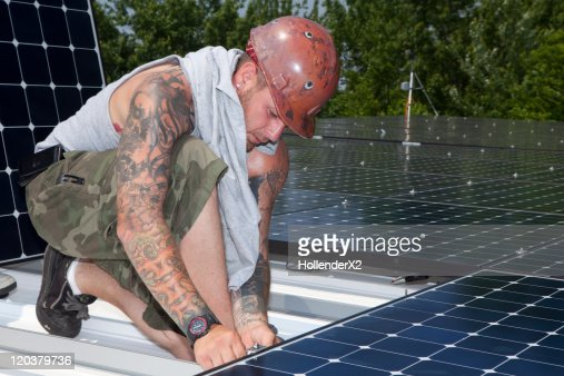 Man installing solar panels on roof : Stock-Foto