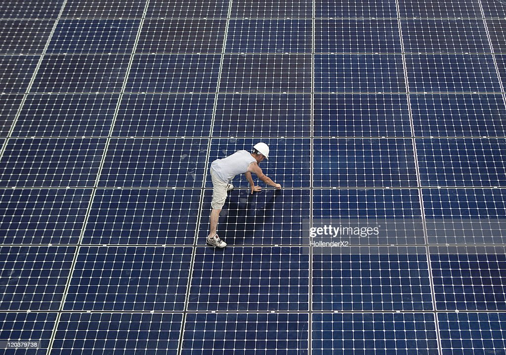Man installing solar panels on rooftop : Stock Photo