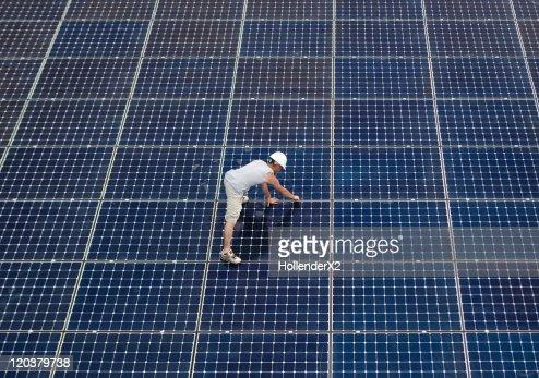Man installing solar panels on rooftop : Stock Photo