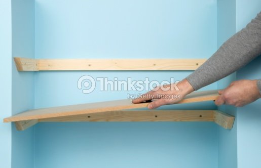 man installing wooden shelf on battens attached to blue wall stock photo thinkstock. Black Bedroom Furniture Sets. Home Design Ideas