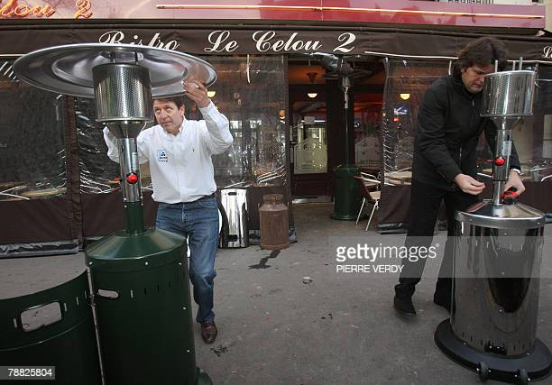 A man installs a heater on a Paris cafe terrace where people can smoke 08 January 2008 after cafes restaurants and nightclubs across France became...