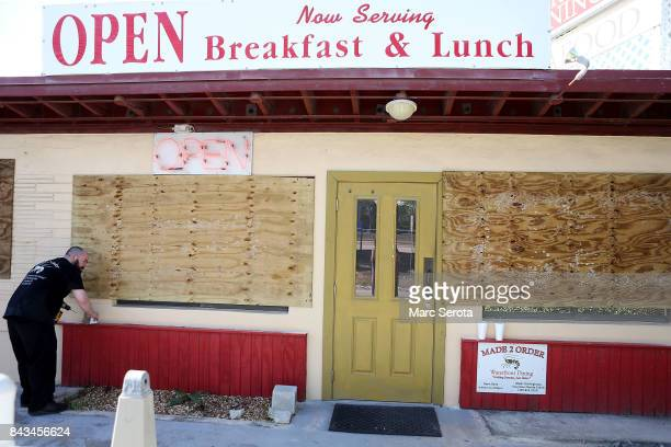 A man installs hurricane shutters at the Made 2 Order Restuarant in Islamorada Florida on September 6 2017 The storm has grown to a category 5 and is...