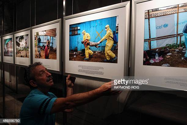 A man installs photos by Daniel Berehulak during the 27th 'Visa pour l'Image' international festival of photojournalism in Perpignan on August 25...