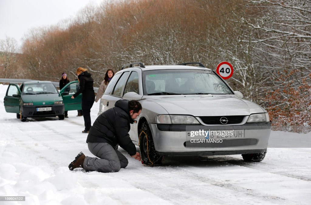 A man installs snow chains on his car to drive on a snow-covered road in Pineda de la Sierra, near Burgos, on January 23, 2013. AFP PHOTO/ CESAR MANSO