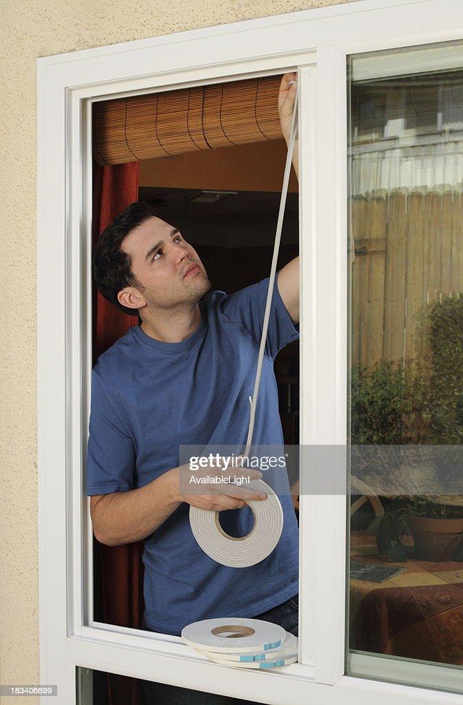 Homme installe calfeutrage dans la fenêtre : Photo