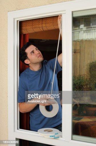 Man Installs Weather Stripping in Window