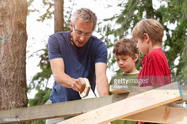 Man instructing boys how to use a saw