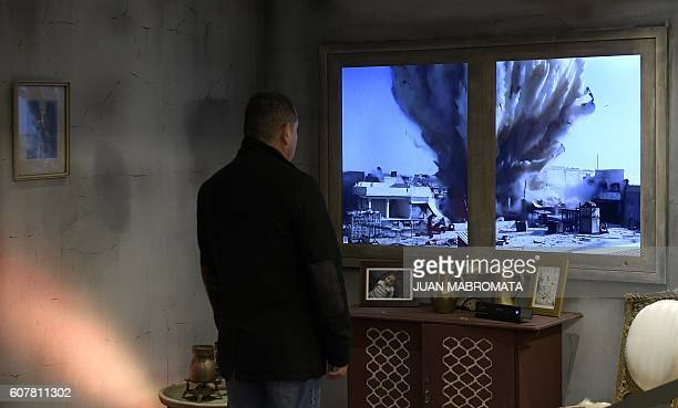 TOPSHOT A man interacts with an installation by Amnesty International depicting a Syrian home during the war in a passage of Buenos Aires' subway on...