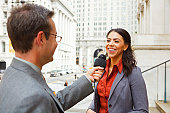 A man with a microphone interviewing a smiling professionally dressed woman on the steps of a building in the city.