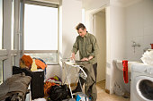 Man ironing clothing in laundry room
