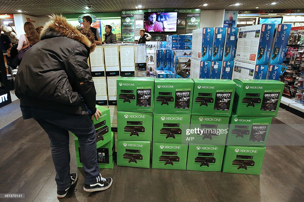 A man is about to buy the new XBox One game console on November 22, 2013 in Paris. Gamers in more than a dozen countries started snapping up new-generation Xbox One consoles Friday as Microsoft battled Sony to be at the heart of Internet age home entertainment. AFP PHOTO / Marion Ruszniewski