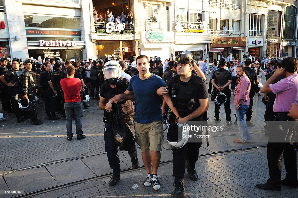 A man is arrested, as Turkish police battle anti-government protestors along the Istiklal shopping street near Taksim Square on July 8, 2013 in Istanbul, Turkey. The protests began in late May over the Gezi Park redevelopment project and saving the park trees adjacent to Taksim Square but swiftly turned into a protest aimed at Prime Minister Recep Tayyip Erdogan and what protestors call his increasingly authoritarian rule. The protest spread to dozens of cities in Turkey, in secular anger against Mr. Erdogan and his Islam-rooted Justice and Development Party (AKP).