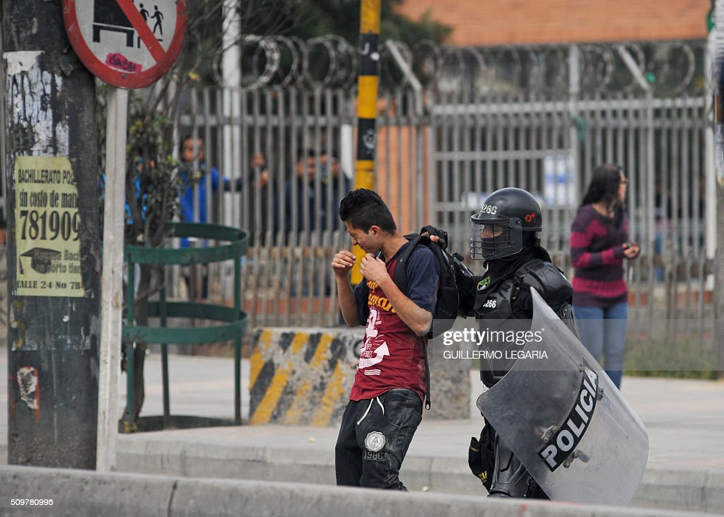 A man is arrested during a protest at the 'Transmilenio' station in southern Bogota, Colombia, on February 12, 2016. Users of public transportation blocked roads to protest what they consider poor service and high cost. Amid the protest several buses were damaged as well as stations destroyed and several demonstrators were detained by police after clashes. AFP PHOTO / GUILLERMO LEGARIA / AFP / GUILLERMO LEGARIA
