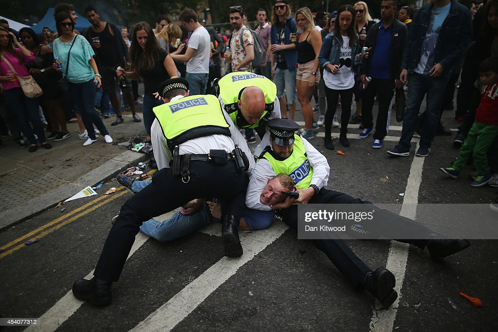 A man is arrested during the Notting Hill Carnival on August 24, 2014 in London, England. The Notting Hill Carnival is the largest street festival in Europe and was first held in 1964 by the Afro-Caribbean community. Over the bank holiday weekend the streets come alive to steel bands, colourful floats and costumed performers as members of the public flood into the area to join in the celebrations.