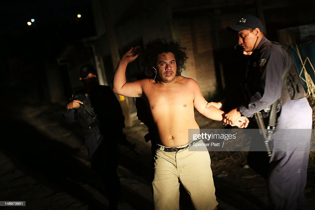 A man is arrested for fighting in a neighborhood with heavy gang violence on July 20, 2012 in Tegucigalpa, Honduras. Honduras now has the highest per capita murder rate in the world and its capital city, Tegucigalpa, is plagued by violence, poverty, homelessness and sexual assaults. With an estimated 80% of the cocaine entering the United States now being trans-shipped through Honduras, the violence on the streets is a spillover from the ramped rise in narco-trafficking.