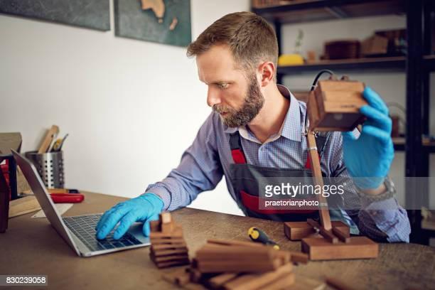 Mann ist eine hölzerne Lampe in einer kleinen Familie Zimmermann-Fabrik Montage