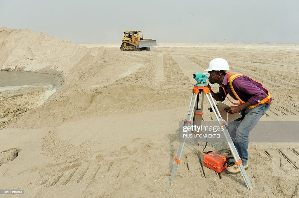 A man is at work, on January 31, 2013 in Lagos, at the building site of the three and a half kilometre long sea defence barrier called 'The Great Wall of Lagos' built to shield from coastal erosion Eko Atlantic, a new city born from the Altantic ocean in Lagos. Nigeria's President Goodluck Jonathan and former US President Bill Clinton dedicated on February 21, 2013 the new 5-million-square-metre Eko Atlantic City, which is to be the first modern smart city in Africa to be built on reclaimed land from the Atlantic Ocean.