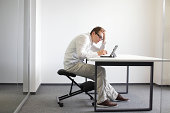 Young man is bent over his tablet in his office,seating on kneeling chair Bad sitting posture at work