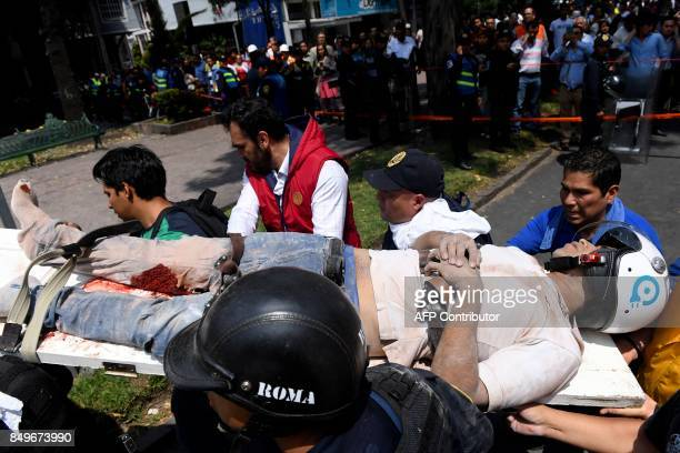 A man is carried on a stretcher after being pulled out of the rubble following a quake in Mexico City on September 19 2017 A powerful earthquake...