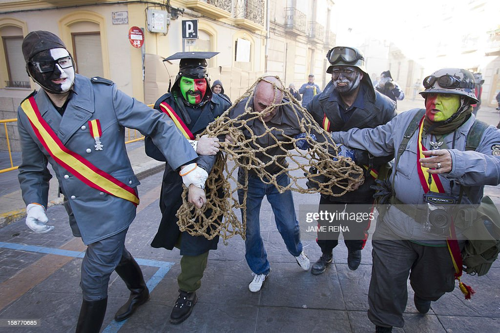 A man is caught by military dressed men as they take part in the battle of 'Enfarinats', a floor fight in the town of Ibi, in the south-eastern Spain on December 28, 2012. For 200 years Ibi's citizens annually celebrate with a battle using flour, eggs and firecrackers outside the city townhall.