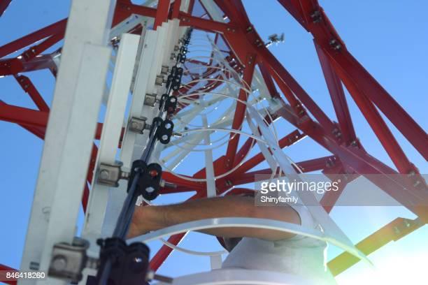 Mann ist einen Hochleistungs-Stromleitung Turm klettern.