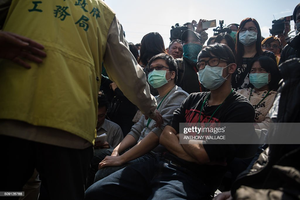 A man (C) is comforted as he attends a briefing to relatives by Tainan's Mayor William Lai and Cheng Ming-chang, president of Tainan civil engineers association (both not seen) on the rescue operation of a building which collapsed in the 6.4 magnitude earthquake, in the southern Taiwanese city of Tainan on February 9, 2016. Rescuers deployed heavy machinery on February 9 in a renewed effort to locate more than 100 people trapped in the rubble of a Taiwan apartment complex felled by an earthquake as the 72-hour 'golden window' for finding survivors passed. AFP PHOTO / ANTHONY WALLACE / AFP / ANTHONY WALLACE