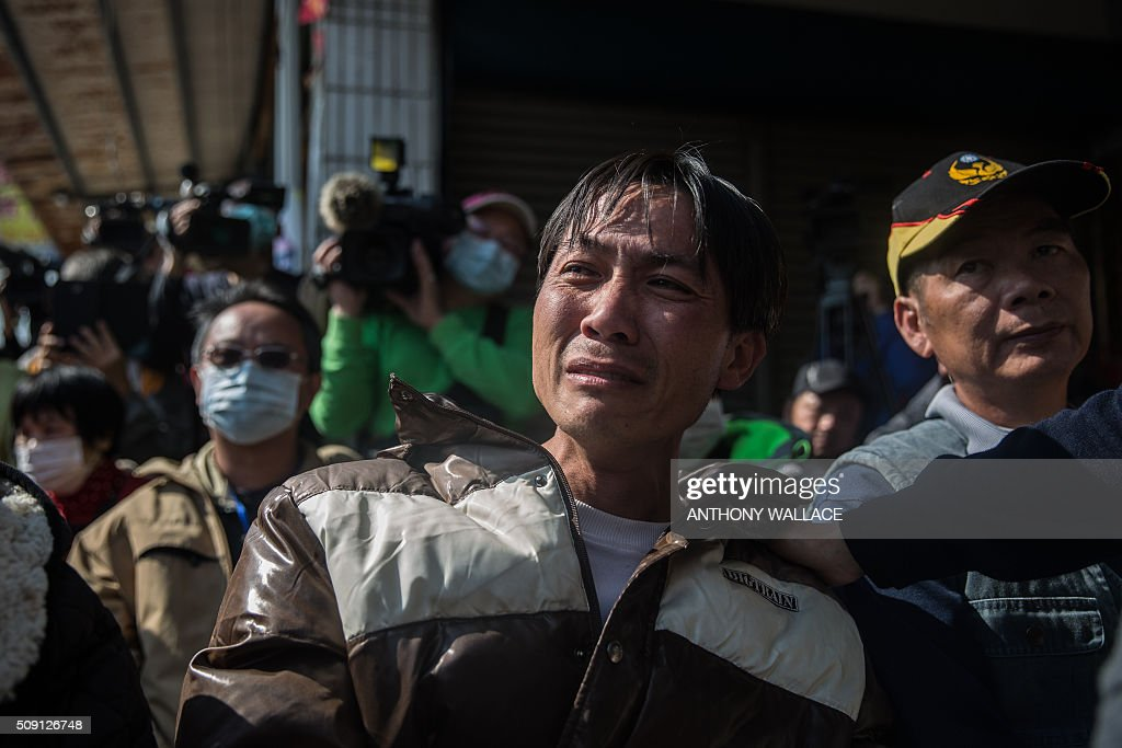 A man (C) is comforted as he cries during a briefing to relatives by Tainan's Mayor William Lai and Cheng Ming-chang, president of Tainan civil engineers association (both not seen), on the rescue operation of a building which collapsed in the 6.4 magnitude earthquake, in the southern Taiwanese city of Tainan on February 9, 2016. Rescuers deployed heavy machinery on February 9 in a renewed effort to locate more than 100 people trapped in the rubble of a Taiwan apartment complex felled by an earthquake as the 72-hour 'golden window' for finding survivors passed. AFP PHOTO / ANTHONY WALLACE / AFP / ANTHONY WALLACE