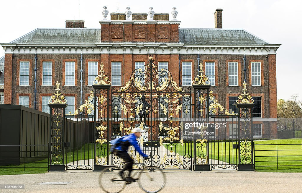 A man is cycling on his bicycle at Kensington Palace with its famous golden gate where people put down flowers and candles when Princess Lady Diana...