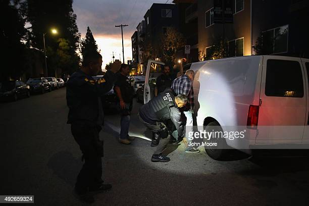 A man is detained by Immigration and Customs Enforcement agents early on October 14 2015 in Los Angeles California ICE agents said the undocumented...