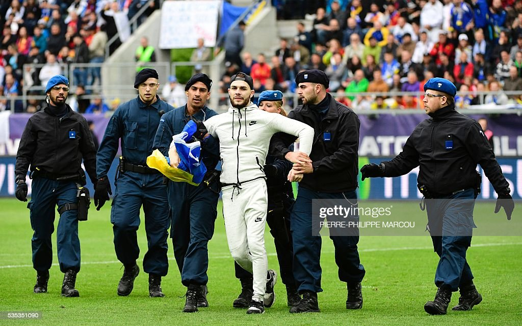 A man is detained by the stadium security during the friendly football match between Spain and Bosnia and Herzegovina at the AFG Arena in St Gallen, Switzerland, on May 29, 2016, in preparation for the upcoming Euro 2016 European football championship. / AFP / PIERRE
