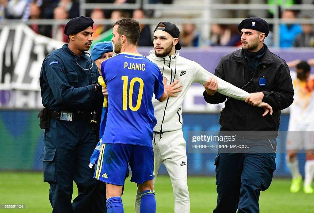 A man is detained by the stadium security members during the friendly football match between Spain and Bosnia and Herzegovina at the AFG Arena in St Gallen, Switzerland, on May 29, 2016, in preparation for the upcoming Euro 2016 European football championship. / AFP / PIERRE
