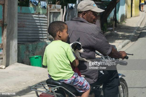Santa Domingo Dominican Republic November 30 2012 A man is driving a motorbike while a young boy holding a dog is sitting behind him in the poor...