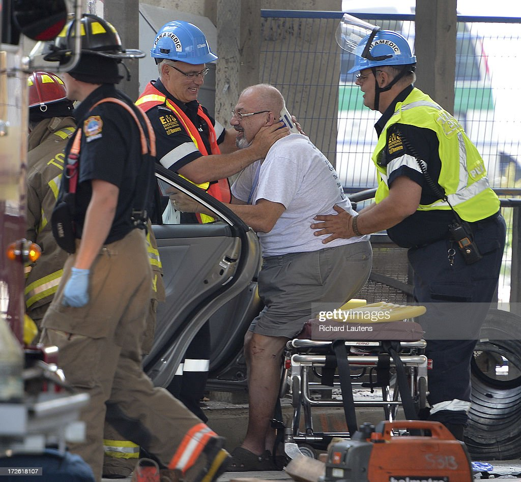 TORONTO, ON - JULY 3 - A man is eased out of the car from New Jersey. A black crossover vehicle with dealer plates and a silver sedan from New Jersey collided at the intersection of Bay and Lakeshore in Toronto just after the noon hour. At least 5 were taken by stretcher into waiting ambulances. One man, in the driver seat of the sedan had to be cut out of the car with the jaws of life by the fire department.