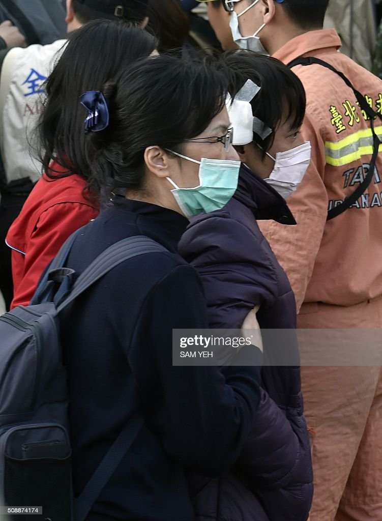 A man (R) is escorted by volunteer workers after his daughter was confirmed dead during an earthquake at the collapsed Wei Kuan complex building in Tainan, southern Taiwan, on February 7, 2016. Rescuers raced on February 7 to free more than 120 people buried under the rubble of an apartment complex felled by an earthquake in southern Taiwan that left 24 confirmed dead, as an investigation began into the collapse. AFP PHOTO / Sam Yeh / AFP / SAM YEH