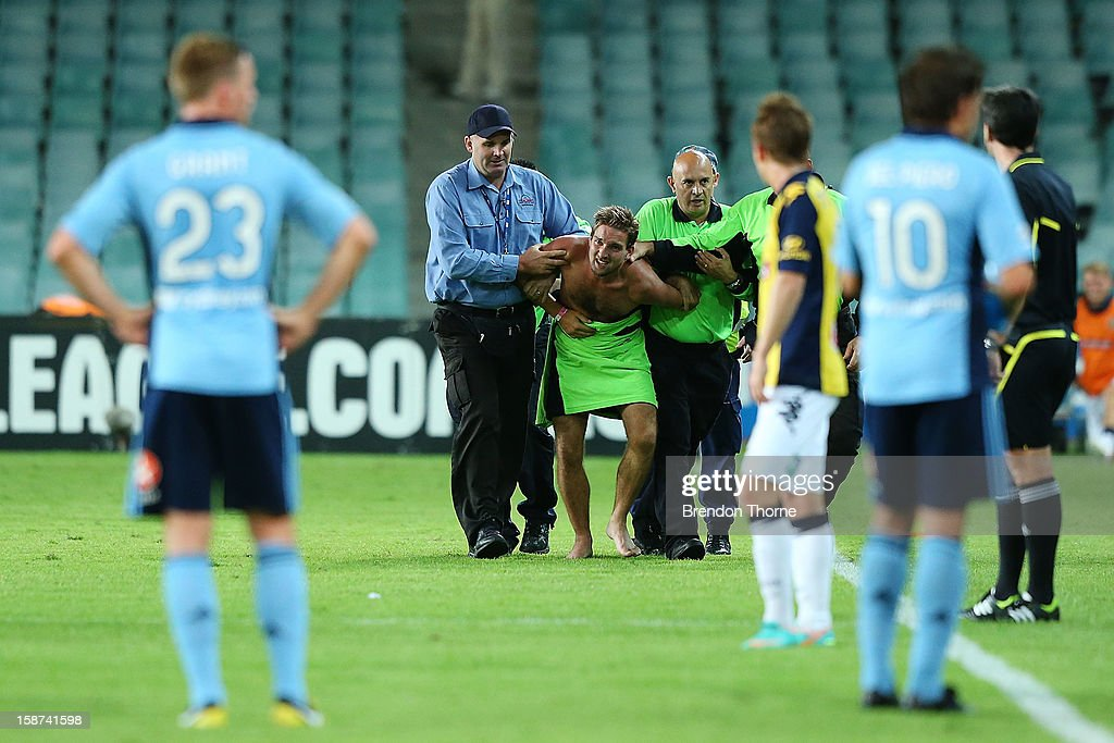 A man is escorted from the field of play during the round 13 A-League match between Sydney FC and the Central Coast Mariners at Allianz Stadium on December 27, 2012 in Sydney, Australia.