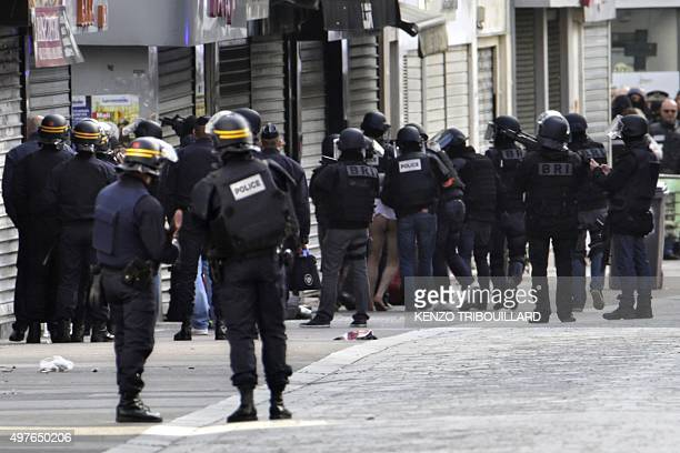 A man is evacuated after being arrested by French policemen in the northern Paris suburb of SaintDenis city center on November 18 as French Police...