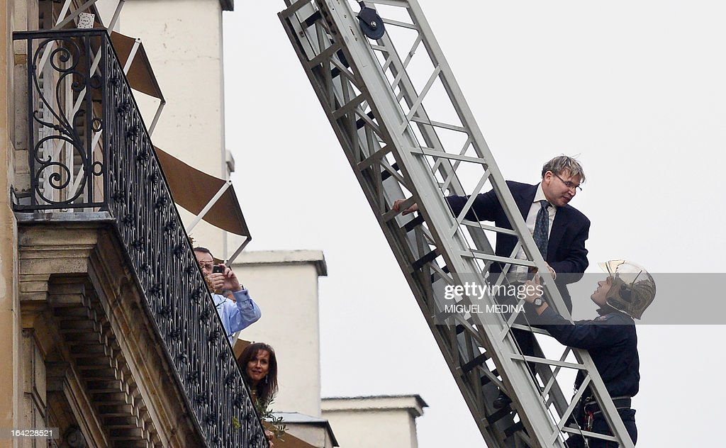 A man (2ndR) is evacuated by a fireman on March 21, 2013, after succeeding to reach the roof of the US embassy in Paris, in spite of tough security measures. The man, Herve Couasnon, 54, a bus driver from Perigueux, southwestern France, asked to have a meeting with US President Barack Obama, who is today in an official visit in Ramallah, to handle him his CV and to speak about peace. The man succeeded twice in the recent years to circumvent security measures in France.