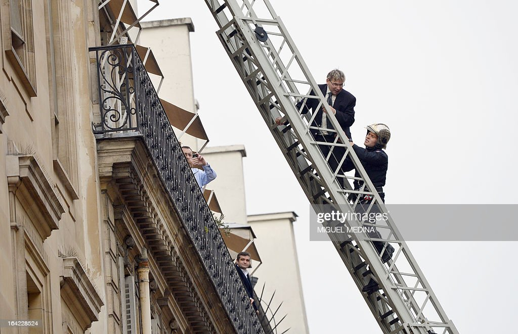 A man (C) is evacuated by a fireman on March 21, 2013, after succeeding to reach the roof of the US embassy in Paris, in spite of tough security measures. The man, Herve Couasnon, 54, a bus driver from Perigueux, southwestern France, asked to have a meeting with US President Barack Obama, who is today in an official visit in Ramallah, to handle him his CV and to speak about peace. The man succeeded twice in the recent years to circumvent security measures in France. AFP PHOTO MIGUEL MEDINA