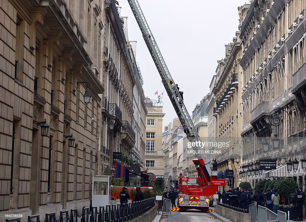 A man (Top L on the ladder) is evacuated by a fireman on March 21, 2013, after succeeding to reach the roof of the US embassy in Paris, in spite of tough security measures. The man, Herve Couasnon, 54, a bus driver from Perigueux, southwestern France, asked to have a meeting with US President Barack Obama, who is today in an official visit in Ramallah, to handle him his CV and to speak about peace. The man succeeded twice in the recent years to circumvent security measures in France. AFP PHOTO MIGUEL MEDINA