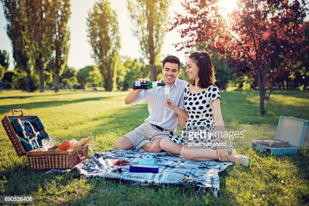Man is filling glass of champagne to his lady at the picnic in the park