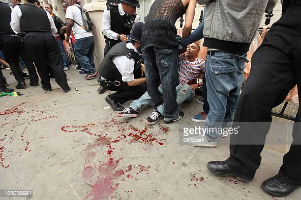 A man is given emergency medical treatment after being stabbed in the stomach at the Notting Hill Carnival on August 29 2011 in London England The...