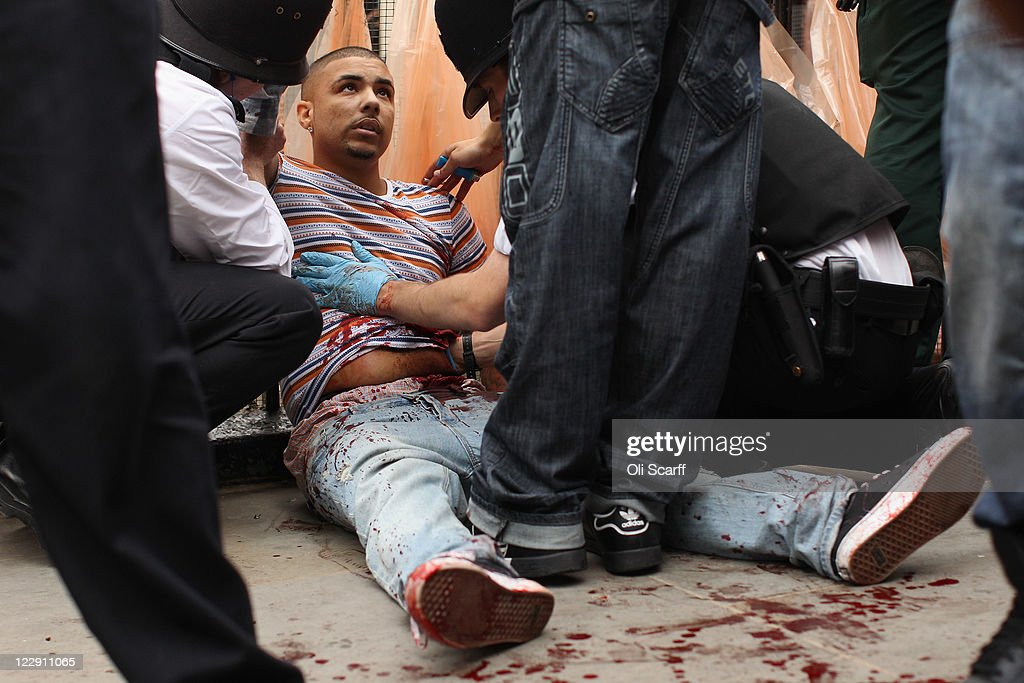 A man is given emergency medical treatment by police officers after being stabbed in the stomach at the Notting Hill Carnival on August 29, 2011 in London, England. The annual carnival, which is the largest of its kind in Europe and is expected to attract around 1 million revellers, has taken place every August Bank Holiday since 1966.