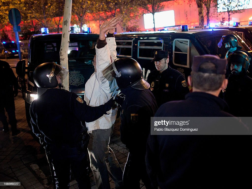 A man is grabbed by riot during a health care workers demonstration outside Madrid Regional Asembly on December 19, 2012 in Madrid, Spain. As of today, health workers unions are calling for a third 48-hour strike against cuts on public health care and the privatization of medical centers and hospitals.