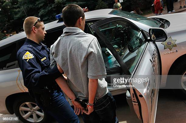 A man is handcuffed and arrested by Aspen police outside the Cannabis Crown 2010 expo April 18 2010 in Aspen Colorado The man was detained by hotel...