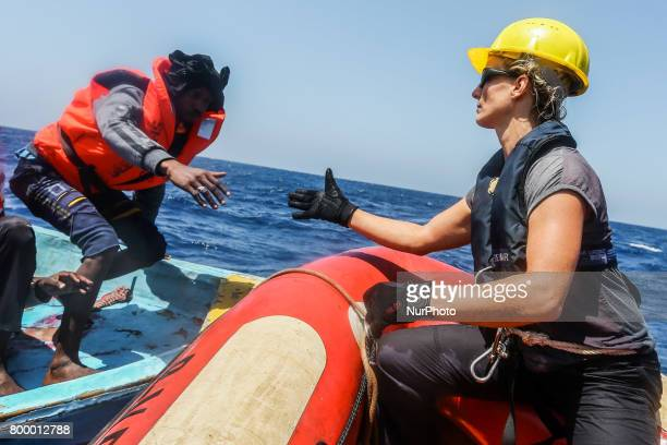 A man is helped off a small rubber boat by crew members from NGO SeaEye on May 19 2017 in international waters off the coast of Libya