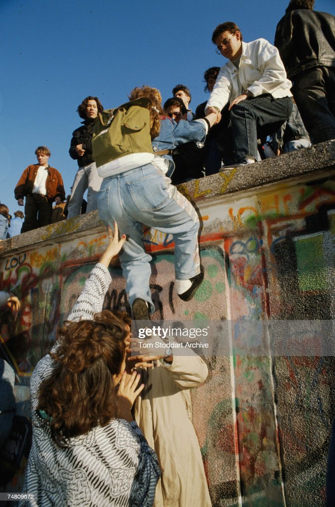A man is helped over the Berlin Wall at the time of the protests which led to its removal, 10th November 1989.