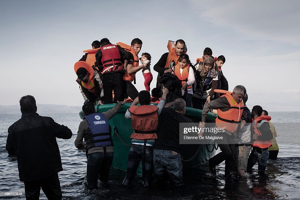 A man is helping out a baby as refugees from Afghanistan and Syria disembark from in a life boat on the shores of Lesbos near Skala Sikaminias Greece...