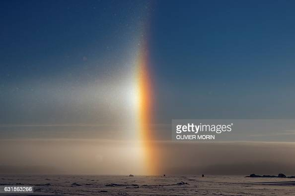 TOPSHOT A man is icefishing near a solar halo on the frozen sea in Vaasa by 15°C on January 15 2017 The Halo is an optical phenomena produced by...